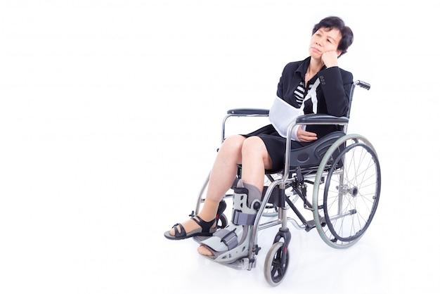 Mulher de negócios asiático com braço quebrado e perna sentada na cadeira de rodas sobre fundo branco