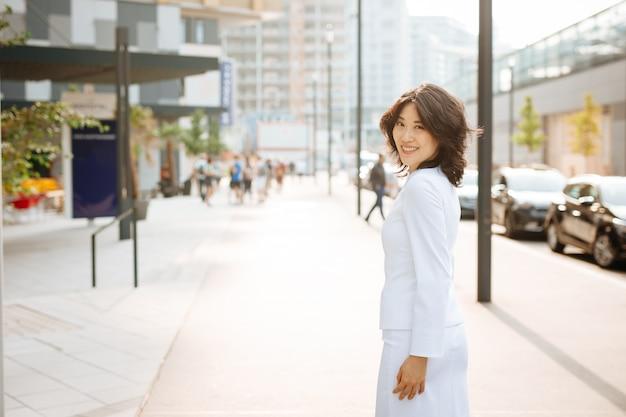Mulher de negócios asiático em pé na rua e olhando para a câmera