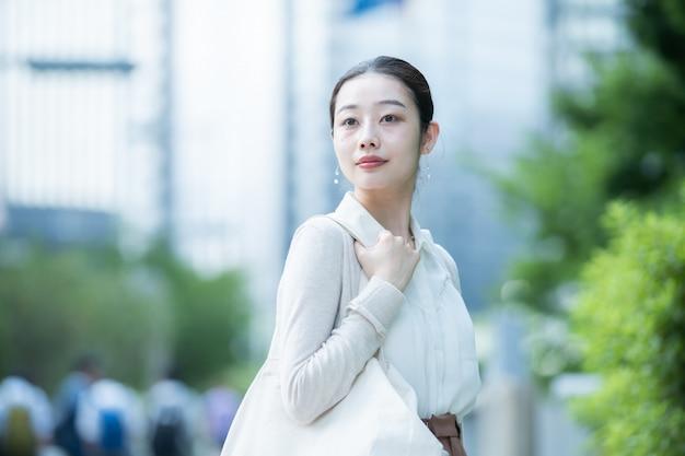 Mulher de negócios asiático na cidade em roupas casuais