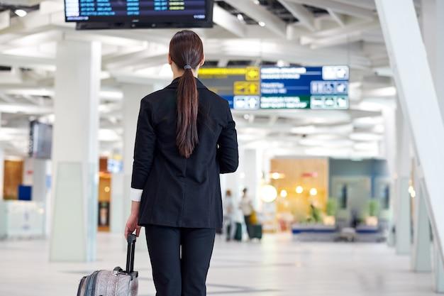 Mulher de negócios asiático no aeroporto com a mala do trole, perto da exibição do voo, olhando a programação de voos