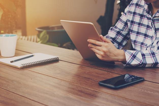 Mulher de negócios asiático no café e usando o tablet na mesa