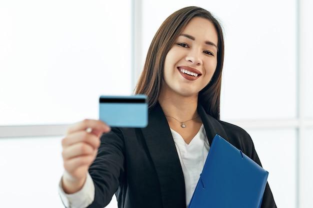 Mulher de negócios asiático segurando um cartão de crédito em branco. retrato de uma menina bonita no escritório moderno