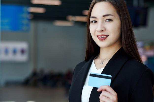 Mulher de negócios asiático segurando um cartão de crédito em branco. retrato de uma menina bonita no escritório ou sala de reunião