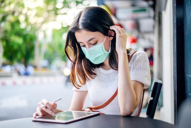 Mulher de negócios asiático sentado em usar máscara cirúrgica usar tablet