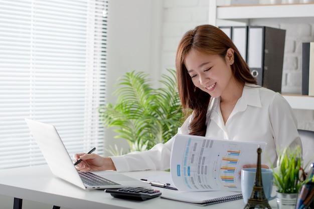 Mulher de negócios asiático sorrindo e feliz. ela trabalha no escritório.