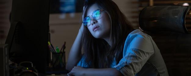Mulher de negócios asiático trabalhando duro e olhando para o gráfico digital na área de trabalho do computador