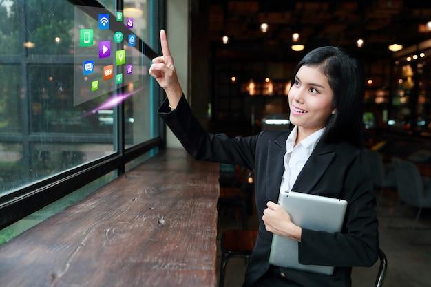 Mulher de negócios asiático usando computador portátil na mesa no café e tocar no ícone do computador no ar