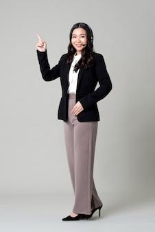 Mulher de negócios asiático usando fone de ouvido microfone como um operador apontando para o espaço vazio