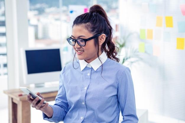 Mulher de negócios asiático usando smartphone no escritório