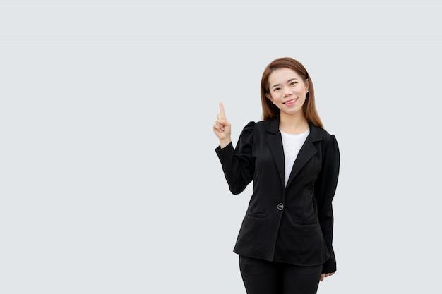 Mulher de negócios asiáticos apontando o dedo, apresentando cabelos longos em terno preto, isolado na cor branca