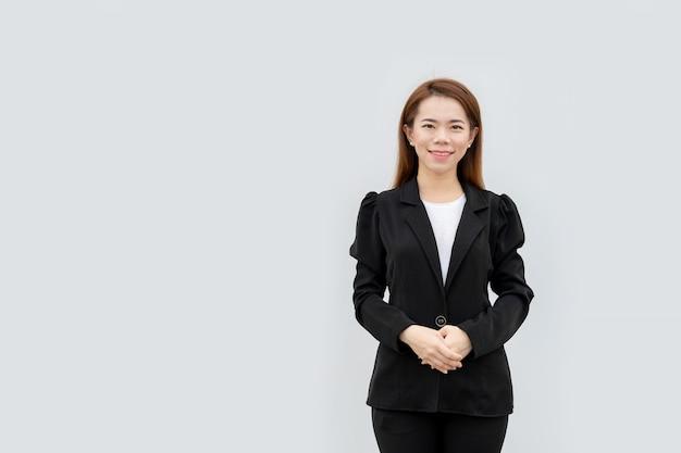 Mulher de negócios asiáticos cruzou as mãos em pé com cabelos longos em terno preto isolado na cor branca