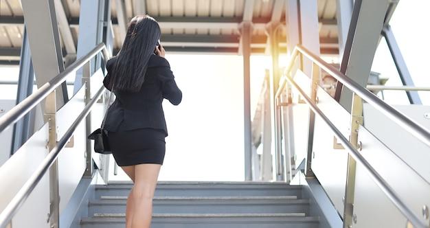 Mulher de negócios asiáticos de vista traseira em terno preto de negócios com máscara de proteção para cuidados de saúde caminhando na passarela pública ao ar livre e usando o smartphone. novo conceito de distanciamento normal e social