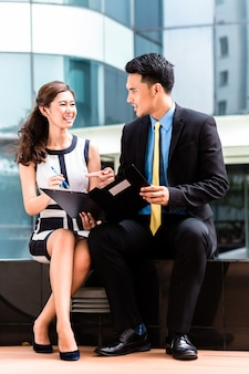 Mulher de negócios asiáticos e homem trabalhando fora, assinando contrato ou fazendo anotações