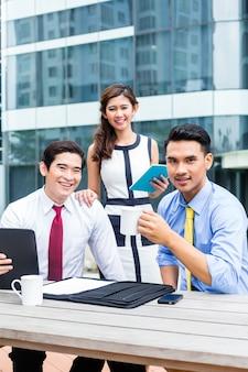 Mulher de negócios asiáticos e homens trabalhando ao ar livre no computador tomando café