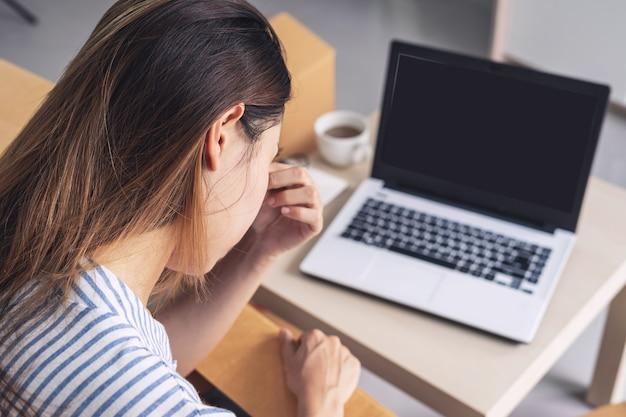 Mulher de negócios asiáticos estressado e frustrado, segurando a cabeça nas mãos