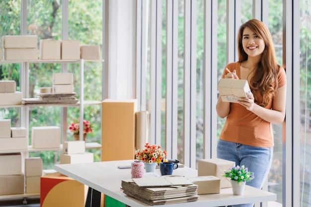 Mulher de negócios asiáticos feliz linda jovem com carinha está segurando uma caixa de encomendas