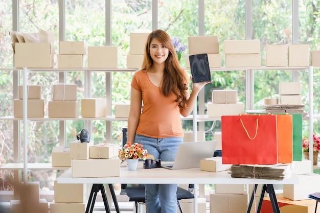 Mulher de negócios asiáticos feliz linda jovem está de pé e segurando um tablet