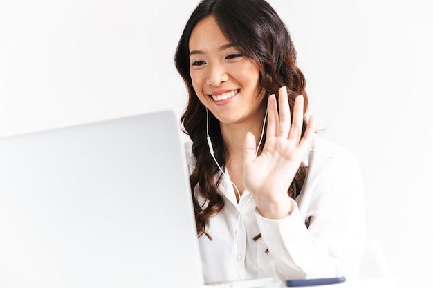 Mulher de negócios asiáticos feliz vestindo roupas de escritório, acenando para o laptop, durante a chamada de vídeo ou conferência on-line
