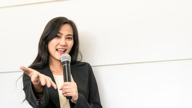Mulher de negócios asiáticos feliz vestindo suite está falando com microfone e apresentando ao público.