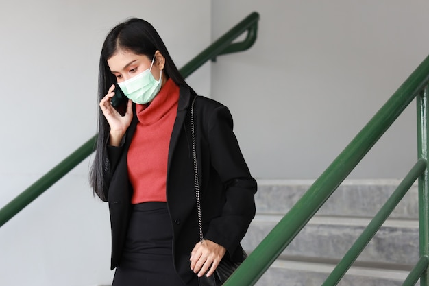 Mulher de negócios asiáticos jovem em terno preto de negócios com máscara de proteção para cuidados de saúde caminhando na passarela pública ao ar livre e usando o smartphone. novo conceito de distanciamento normal e social