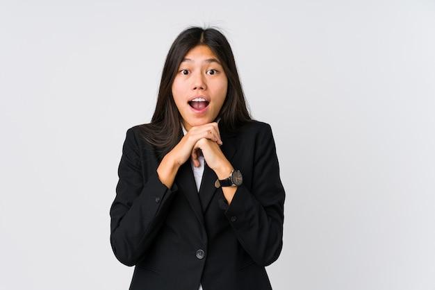 Mulher de negócios asiáticos jovem rezando para ter sorte, espantada e abrindo a boca, olhando para a frente.