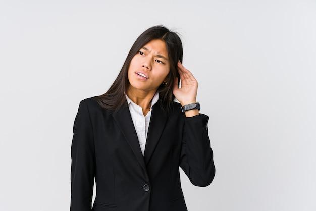 Mulher de negócios asiáticos jovem tentando ouvir uma fofoca.