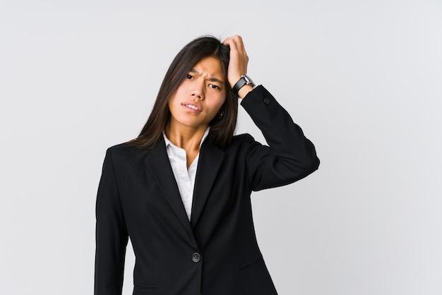 Mulher de negócios asiáticos jovens cansada e muito sonolenta, mantendo a mão na cabeça.