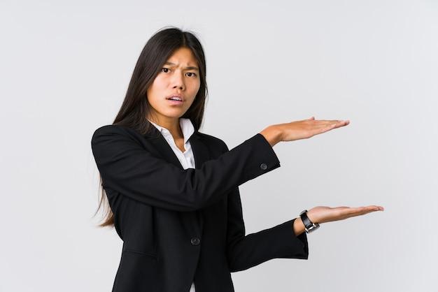 Mulher de negócios asiáticos jovens chocado e surpreso, segurando um espaço de cópia entre as mãos.