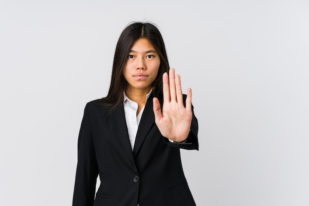Mulher de negócios asiáticos jovens em pé com a mão estendida, mostrando o sinal de stop, impedindo-o.