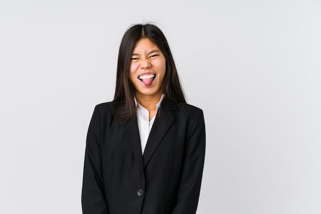 Mulher de negócios asiáticos jovens engraçado e amigável saindo da língua.