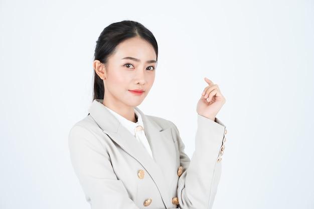 Mulher de negócios asiáticos jovens na camisa branca e terno bege