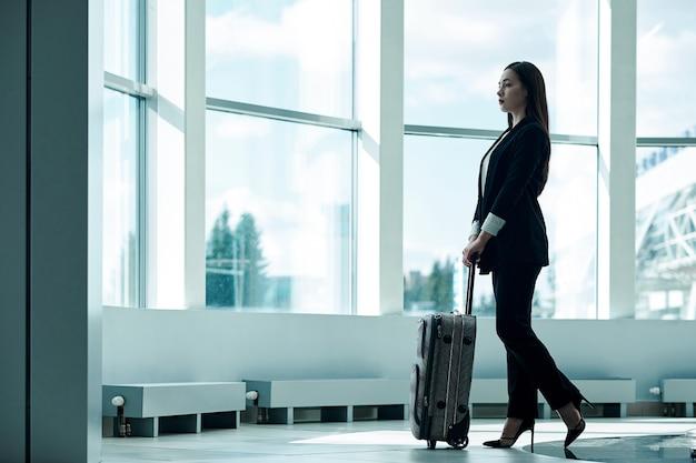 Mulher de negócios asiáticos jovens no aeroporto com saco de carrinho de bagagem, à espera de partida