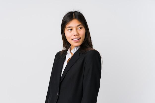 Mulher de negócios asiáticos jovens parece de lado sorrindo, alegre e agradável.