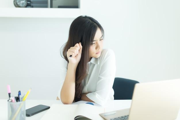 Mulher de negócios asiáticos jovens sorrindo e pensando a ideia sobre o trabalho