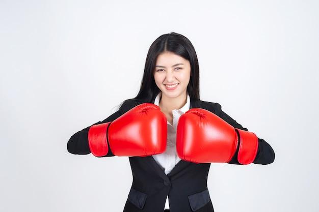 Mulher de negócios asiáticos linda jovem vestindo uma luva de boxe na mão e terno de negócio