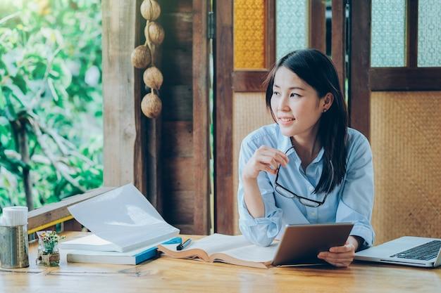 Mulher de negócios asiáticos linda trabalhando com laptop, celular e tablet