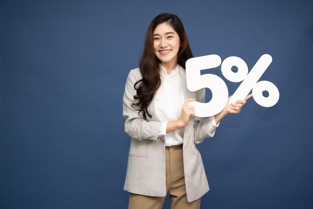 Mulher de negócios asiáticos mostrando e segurando o número de 5% ou cinco por cento isolado sobre a superfície de um azul profundo.