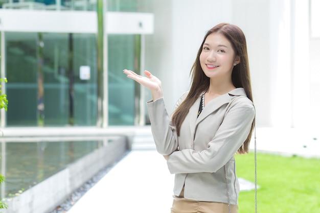 Mulher de negócios asiáticos que trabalha com cabelo comprido e um terno cinza sorri feliz e mostra a mão