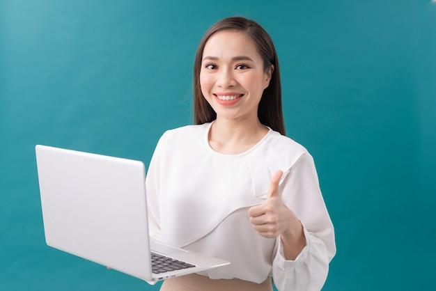 Mulher de negócios asiáticos segurando um laptop e mostrando o polegar enquanto olha para a câmera sobre fundo azul