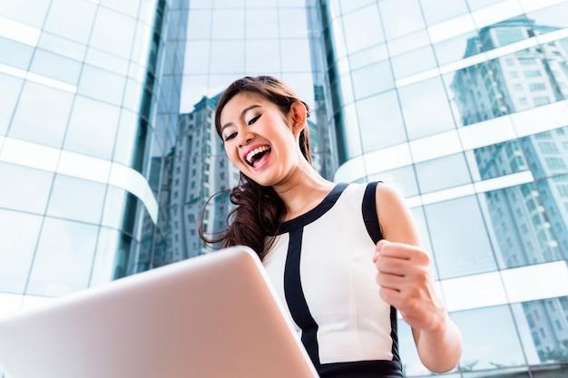 Mulher de negócios asiáticos trabalhando lá fora no computador