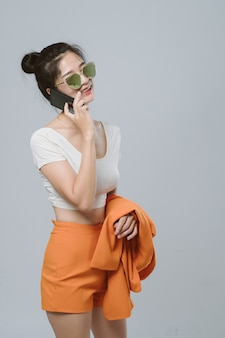 Mulher de negócios asiáticos usando óculos escuros, sorrindo e falando no celular