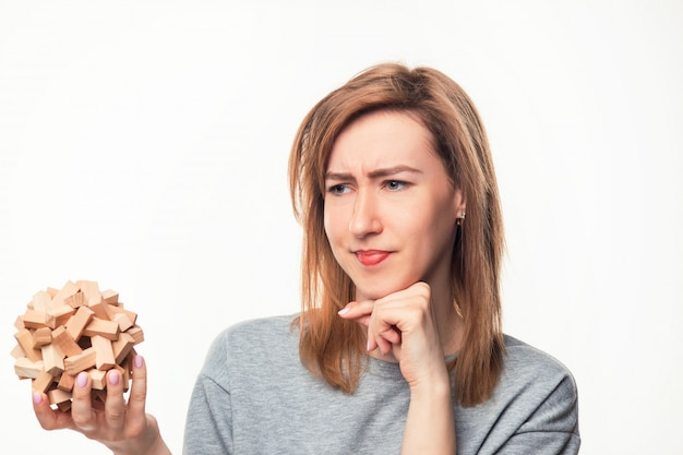 Mulher de negócios atraente 24 anos olhando confuso com quebra-cabeças de madeira.