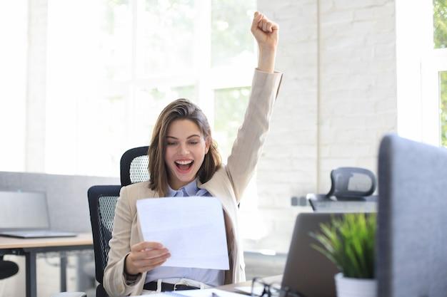 Mulher de negócios atraente alegre ler notícias goog de documentos em papel no escritório.