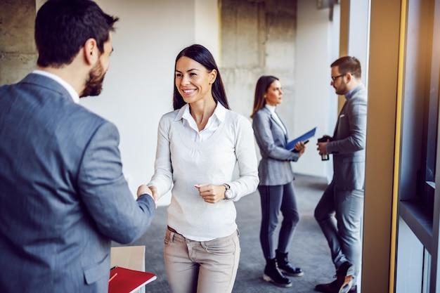 Mulher de negócios atraente caucasiana amigável apertando as mãos de seu novo colega e outros dois colegas conversando. edifício no interior do processo de construção.