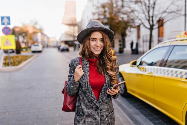 Mulher de negócios atraente correndo para o escritório em um dia quente de outono