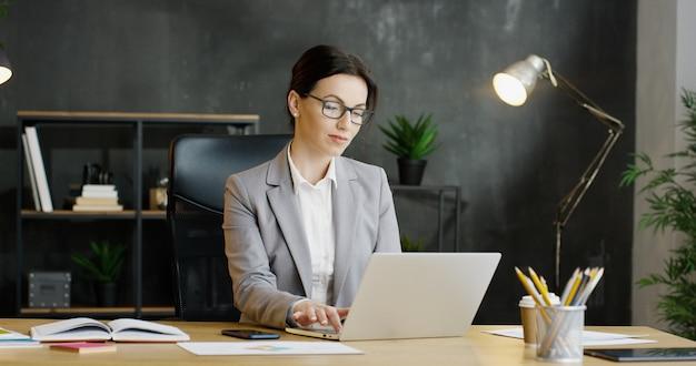 Mulher de negócios atraente digitando no teclado e mensagens de texto, pensando no armário.
