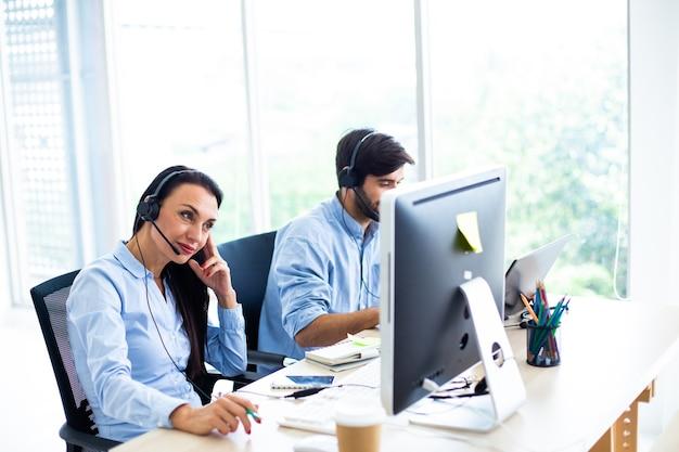 Mulher de negócios atraente e homem de negócios com fones de ouvido sorrindo enquanto trabalha com o computador no escritório