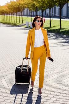 Mulher de negócios atraente elegante terno amarelo puxa uma mala, apressa-se para uma reunião de negócios. mulher de negócios atraente indo em uma viagem de negócios, puxando sua mala ao longo da calçada atrás dela.