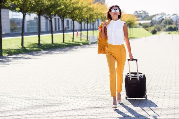 Mulher de negócios atraente elegante terno amarelo puxa uma mala, corre para o aeroporto. mulher de negócios atraente indo em uma viagem de negócios, puxando a mala atrás dela.