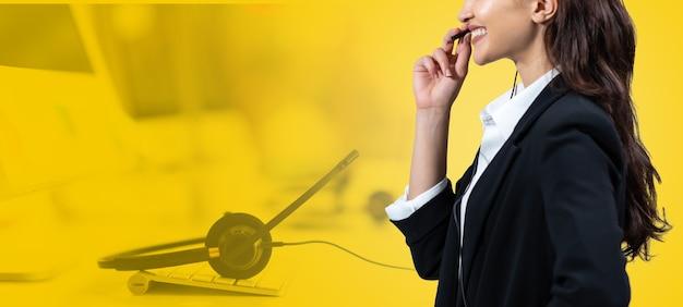 Mulher de negócios atraente em ternos e fones de ouvido sorrindo enquanto trabalha